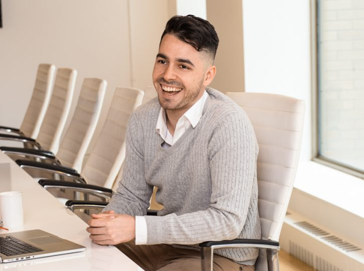 male sits in boardroom with laptop, smiling, for business photographer Toronto 2994