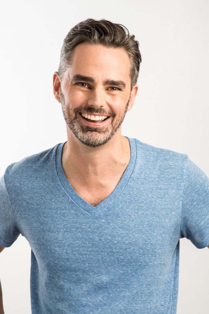 Trevor smiling wearing blue shirt, actor headshots Toronto 0O7C4774