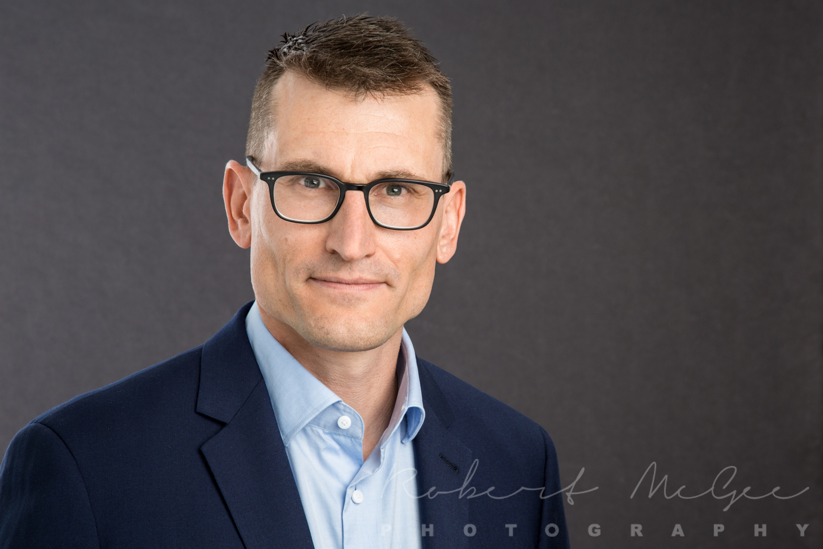 Steve in navy blue business suit against grey backdrop for Toronto professional headshot 0O7C0502