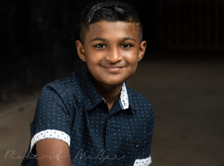 Dontae in blue button shirt smiling for actor headshots for children on dark background 019A5618