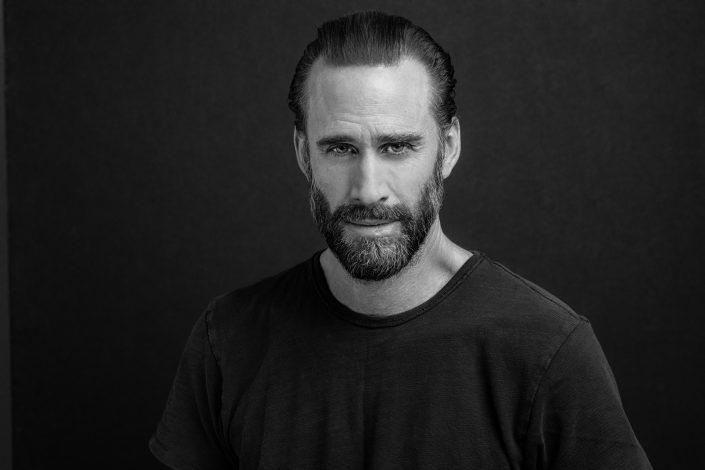 Joseph Fiennes dark shirt on dark background, headshot with beard 019A0252