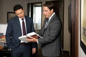 Smitiuch Imjury Law two lawyers confer over book for corporate photography 019A1456